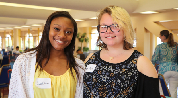 Two interns standing next to each other at an intern fair.